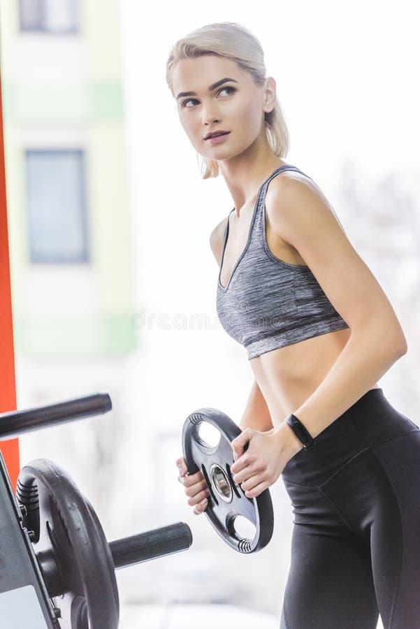 sportive ung kvinna som tillfogar viktplattan till royaltyfria foton