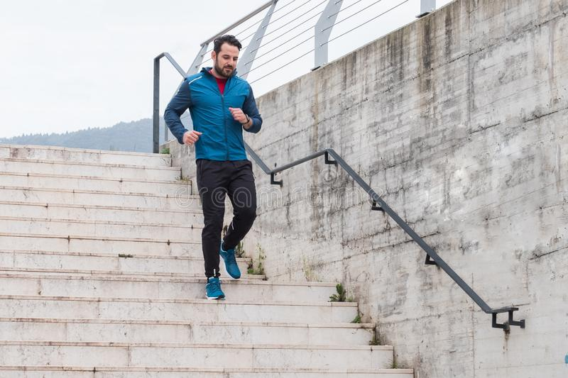 Sportive urban city man running on the stairs stock image