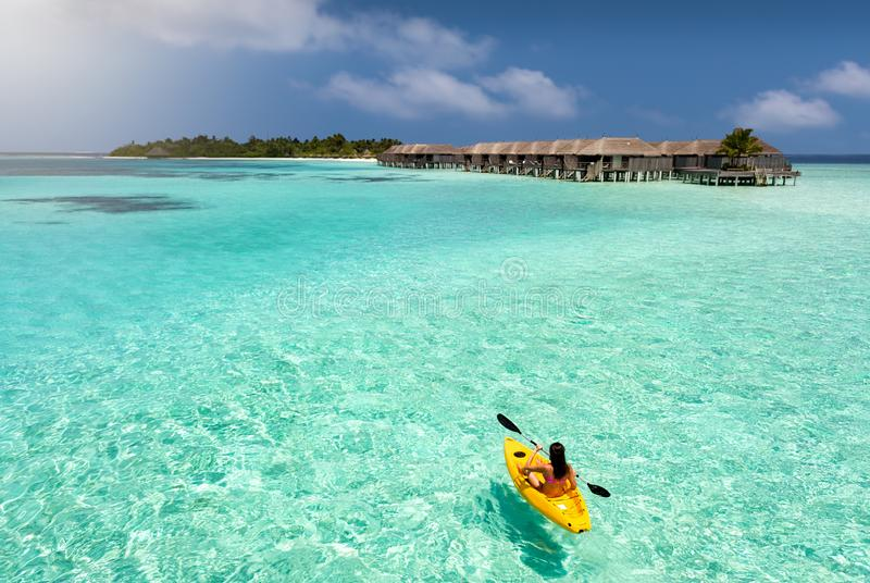 Sportive woman canoeing over the waters of the Maldives royalty free stock images