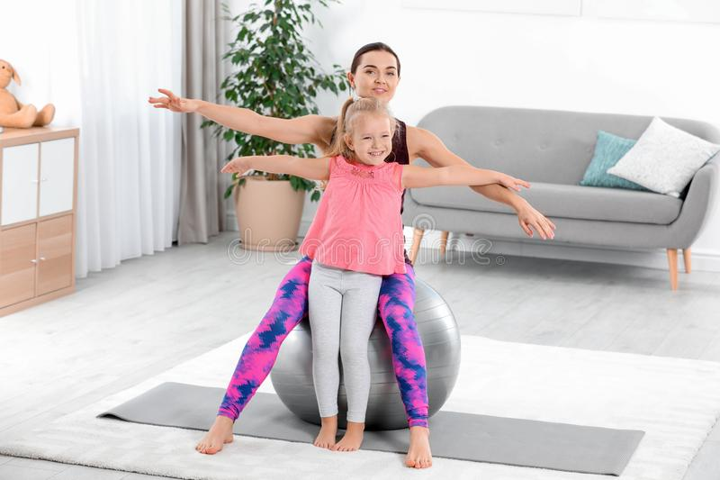 Sportive woman doing fitness exercises. Sportive women doing fitness exercises with daughter at home stock images