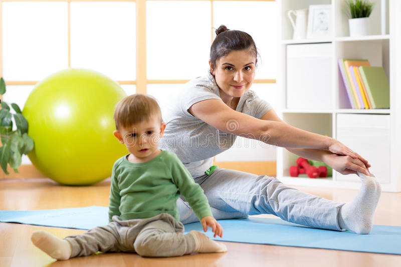 Sportive woman is engaged in fitness and yoga at home. Her son kid by near sitting and playing. Active adult women is engaged in fitness and yoga at home. Her royalty free stock photography