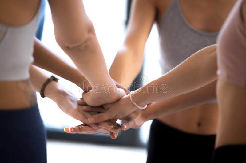 Sportive women stack hands showing team spirit at training royalty free stock images