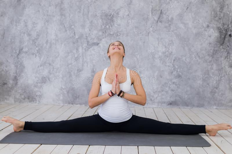 A sportive young girl stretching legs, yoga class. Blonde woman sitting in twine royalty free stock photos
