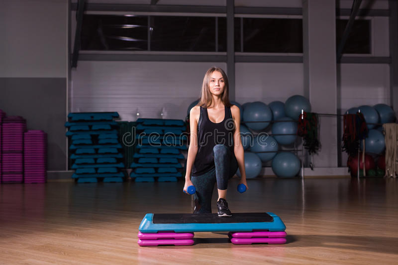 Sportive young woman with beautiful athletic body doing exercises with dumbbells. Fitness, bodybuilding. Healthcare.  stock images