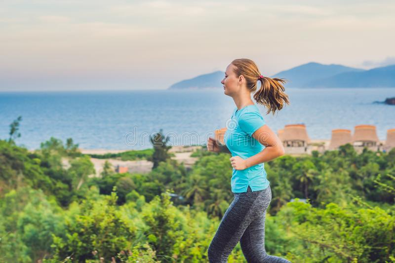 A sportive young woman is engaged in running against the sea royalty free stock images