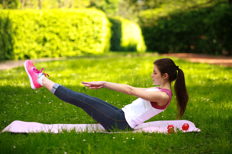 Sportive young woman stretching, doing fitness exercises in park royalty free stock image