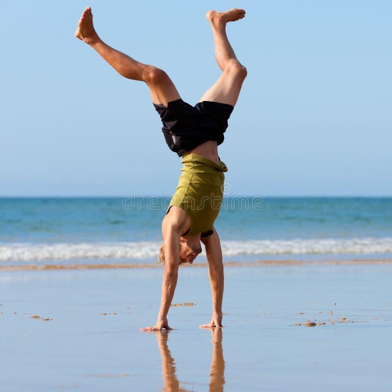 Sportiver Mann, der Gymnastik auf dem Strand tut lizenzfreie stockbilder
