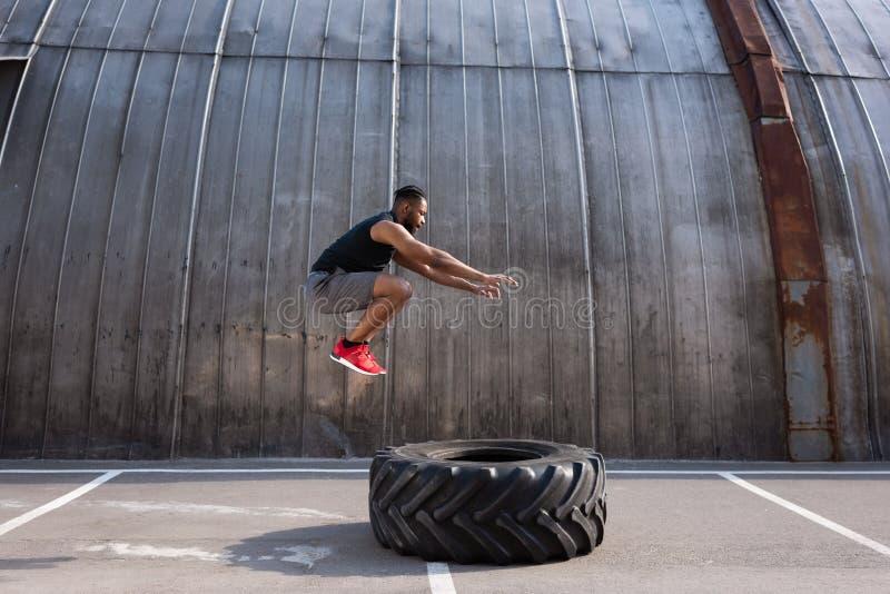 sportivo afroamericano muscolare che salta mentre preparandosi con il pneumatico fotografia stock libera da diritti