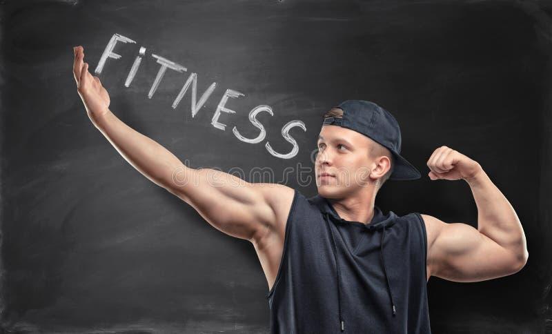Sportivo atletico che sta sui precedenti con la parola & x27; fitness& x27; fotografie stock libere da diritti