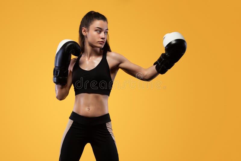 Sportivo, combattimento del pugile della donna nei guanti Su fondo giallo Concetto di forma fisica e di pugilato immagini stock libere da diritti