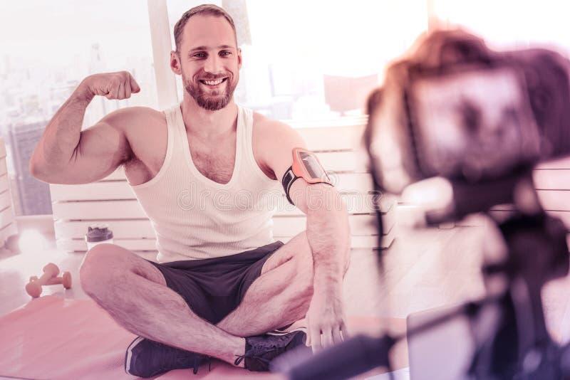Sportivo positivo che mostra il suo muscolo durante la sua radiodiffusione del blog immagini stock