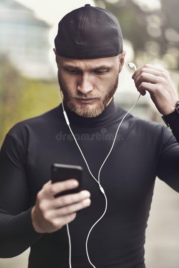 Sportivo professionista in vestito misura pronto all'allenamento Chiuda sul ritratto di musica d'ascolto dell'atleta muscolare at fotografia stock