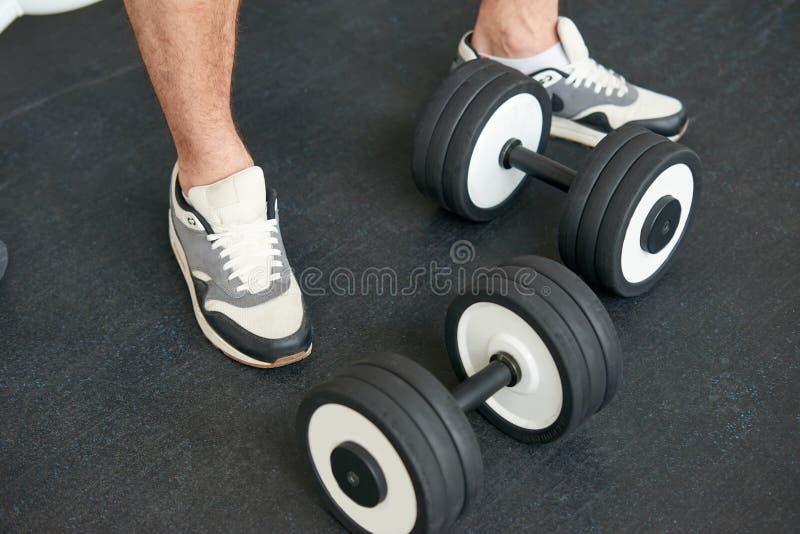 Sportivo in scarpe da tennis che stanno con le teste di legno sul pavimento fotografia stock libera da diritti