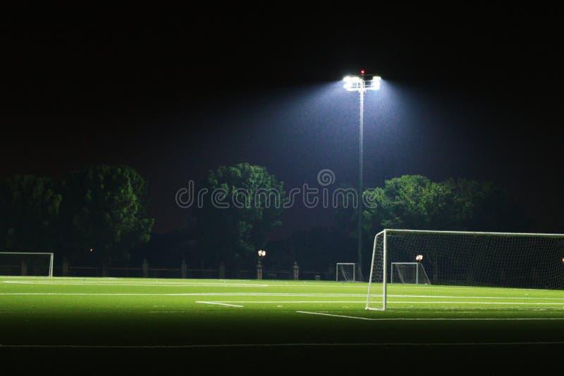 Sportjordning exponerad under ljus i natten arkivbilder