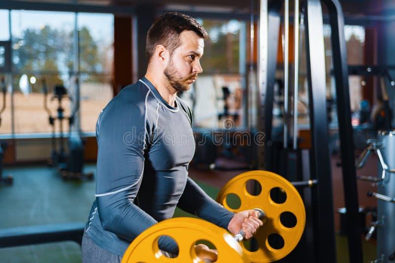 Sportkerl bildet mit einem Barbell aus athletischer Mann, der Gewichtstraining in der Turnhalle tut lizenzfreie stockfotos