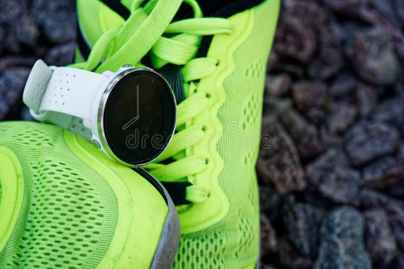 Sportklocka för crossfit och triathlon på de gröna rinnande skorna Smart klocka för spårande daglig aktivitets- och styrkautbildn arkivbild