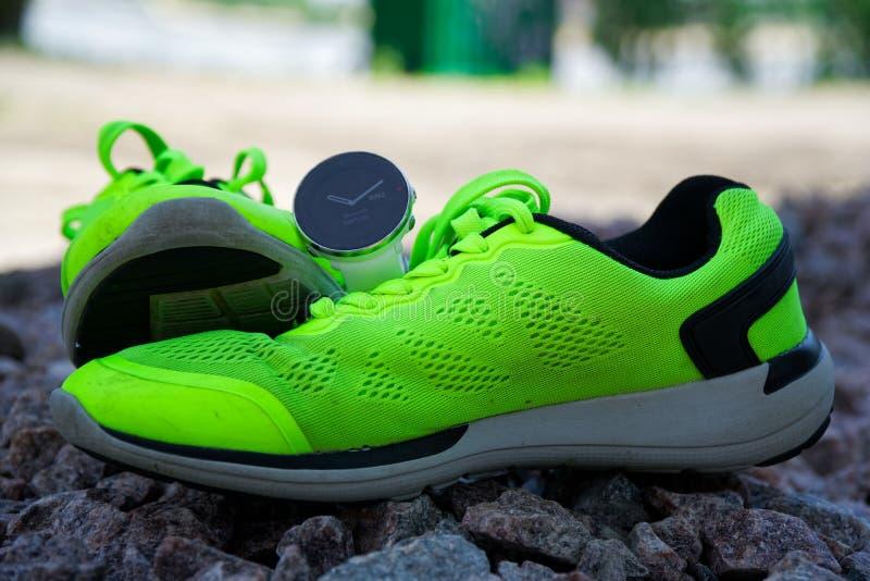 Sportklocka för crossfit och triathlon på de gröna rinnande skorna Smart klocka för spårande daglig aktivitets- och styrkautbildn royaltyfria foton