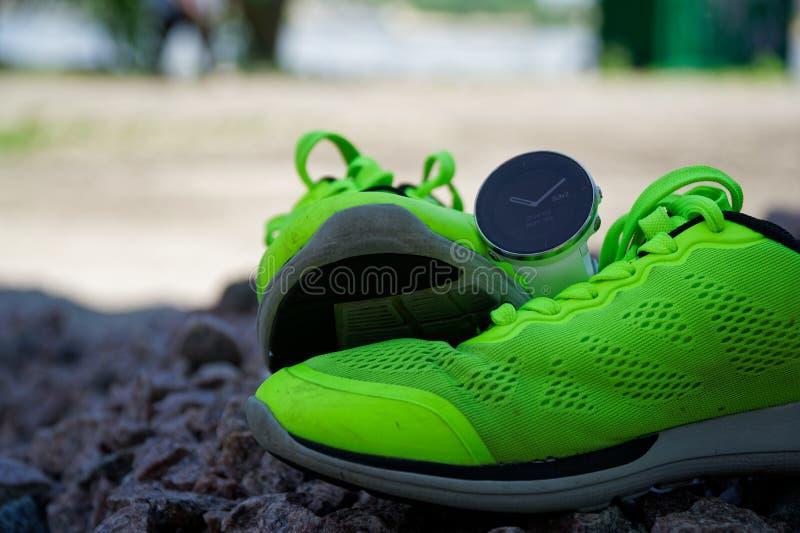 Sportklocka för crossfit och triathlon på de gröna rinnande skorna Smart klocka för spårande daglig aktivitets- och styrkautbildn royaltyfri bild