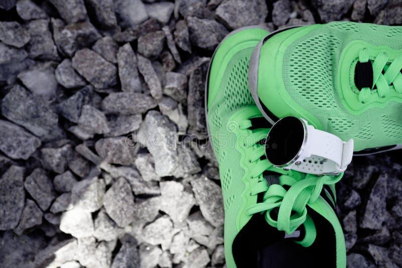 Sportklocka för crossfit och triathlon på de gula rinnande skorna Smart klocka för spårande daglig aktivitets- och styrkautbildni royaltyfri bild