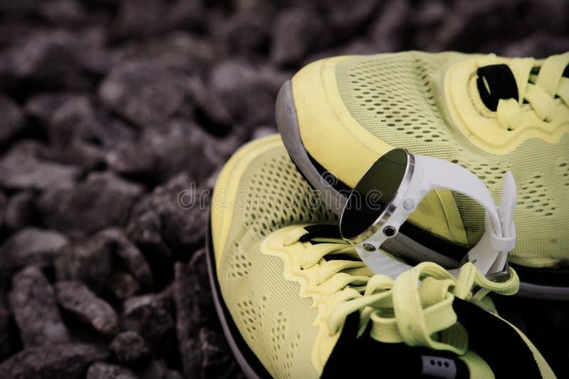 Sportklocka för crossfit och triathlon på de gula rinnande skorna Smart klocka för spårande daglig aktivitets- och styrkautbildni royaltyfria bilder