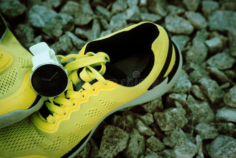 Sportklocka för crossfit och triathlon på de gula rinnande skorna Smart klocka för spårande daglig aktivitets- och styrkautbildni arkivbilder