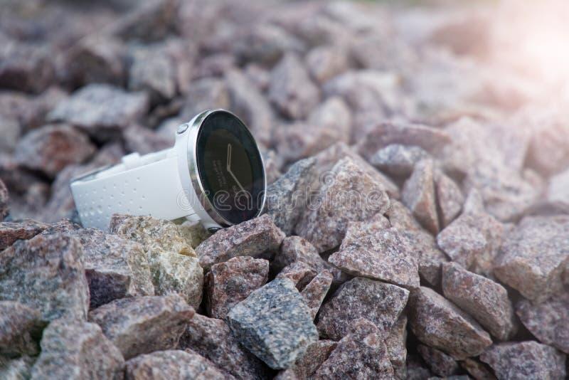 Sportklocka för triathlon på granitgruset Smart klocka för spårande daglig aktivitets- och styrkautbildning Solstrålljus arkivfoto