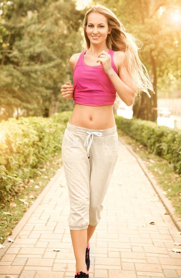 Sportkondition som kör att jogga för ung kvinna arkivbild
