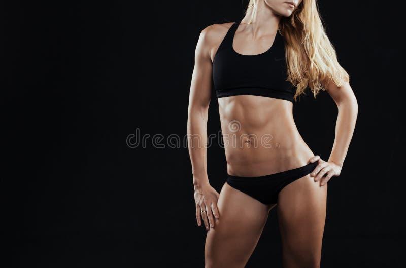 Sportkonditionkvinna med starka muskler på svart bakgrund royaltyfri fotografi