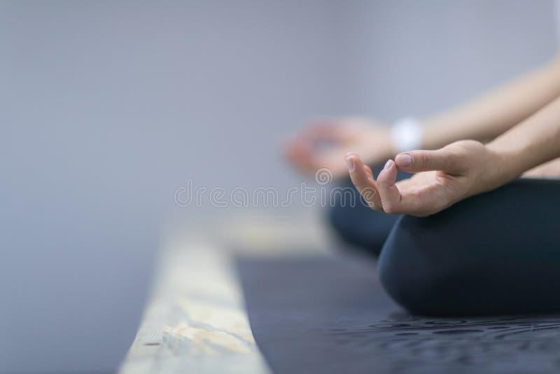 Sportkonditionkvinnan som gör yoga, övar i idrottshallen, den unga sunda flickan för closeupen som sitter Lotus Pose fotografering för bildbyråer