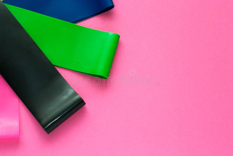 Sportkonzept - stellen Sie von den elastischen Expandern der bunten Eignung für Frau auf rosa Hintergrund ein Gesunder Lebensstil stockfoto