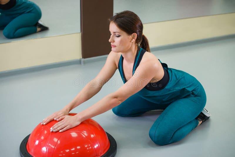 Sportkvinnaövning med en jämviktsboll på idrottshallen Kondition- och livsstilbegrepp fotografering för bildbyråer