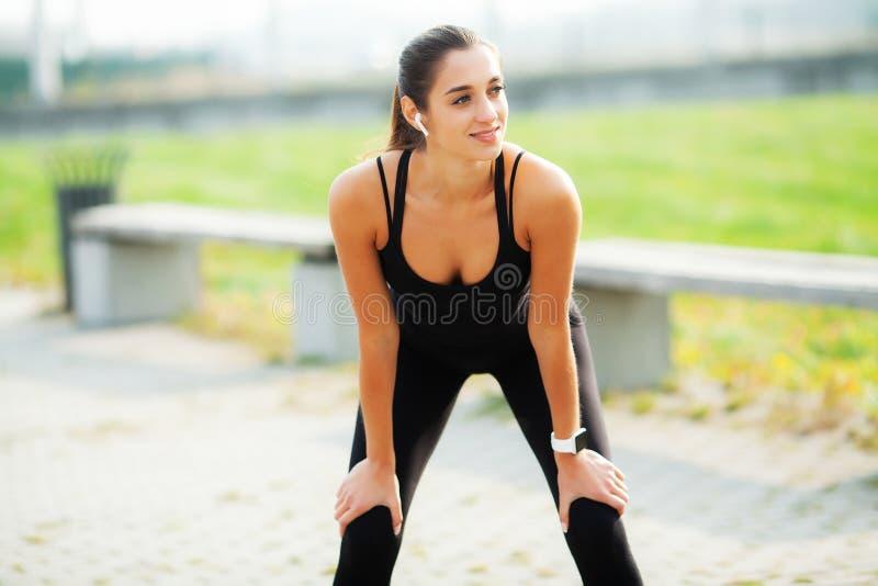 Sportkvinna efter sportövningar i den stads- miljön arkivbild