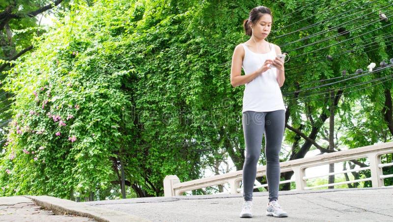 Sportkvinna som använder mobiltelefonspring i Park City den stads- trädgården royaltyfria foton