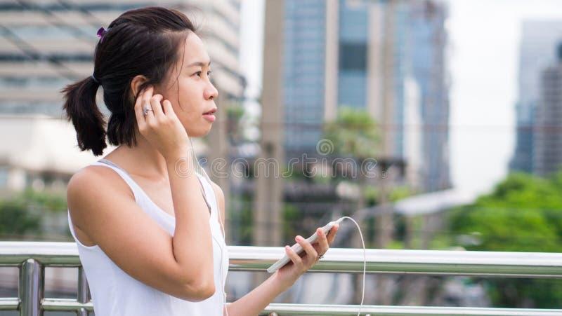 Sportkvinna som använder mobiltelefonspring i stads- byggnad för stad royaltyfri bild