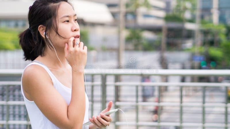 Sportkvinna som använder mobiltelefonspring i stads- byggnad för stad royaltyfri fotografi