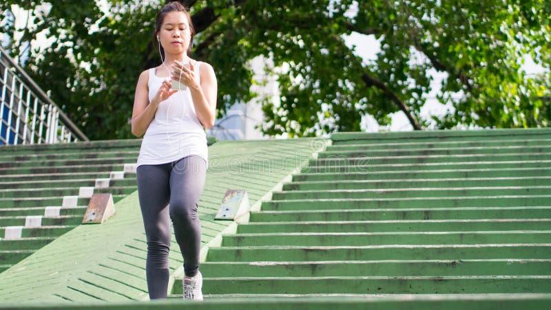 Sportkvinna som använder mobiltelefonspring i stads- byggnad för stad arkivfoto
