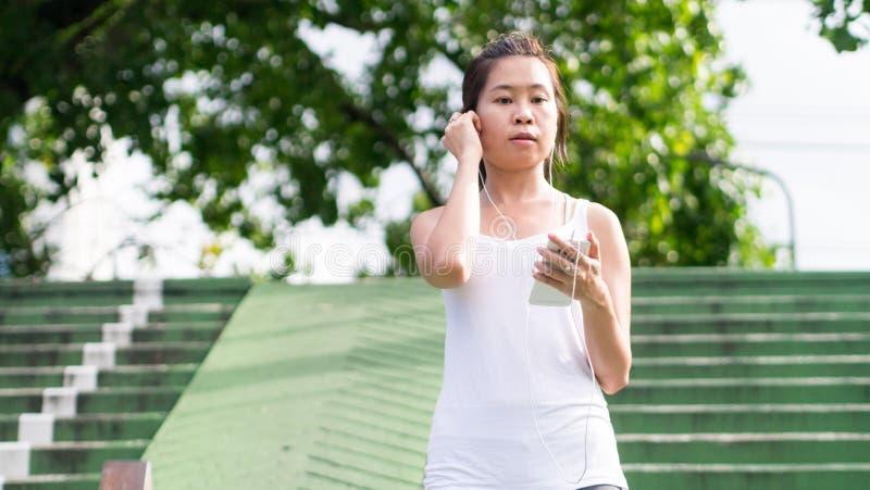 Sportkvinna som använder mobiltelefonspring i stads- byggnad för stad arkivfoton