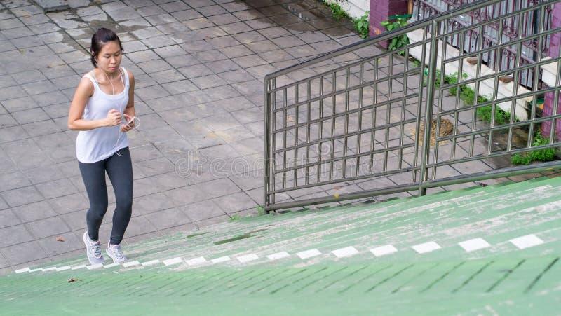 Sportkvinna som använder mobiltelefonspring i stads- byggnad för stad fotografering för bildbyråer