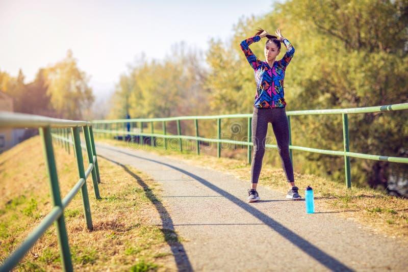 Sportkvinna som får klar att köra och öva utomhus arkivfoton