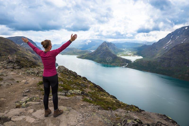 Sportkvinna som fotvandrar på Besseggen Fotvandrare tycker om den härliga sjön och bra väder i Norge arkivfoton