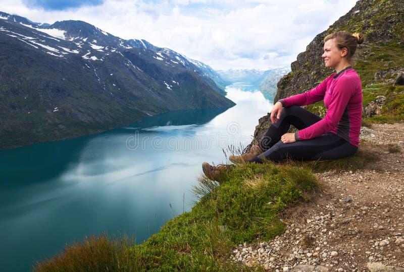 Sportkvinna som fotvandrar på Besseggen Fotvandrare tycker om den härliga sjön och bra väder i Norge arkivbilder