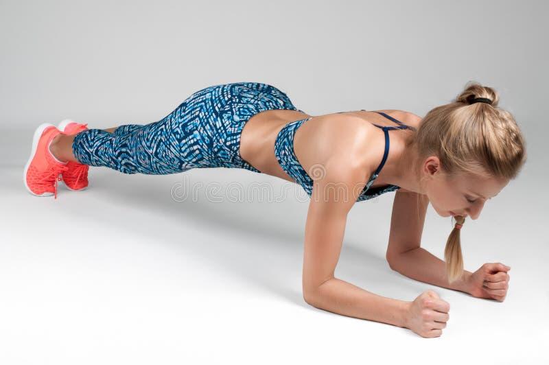 Sportkvinna som gör en plankaövning royaltyfria bilder