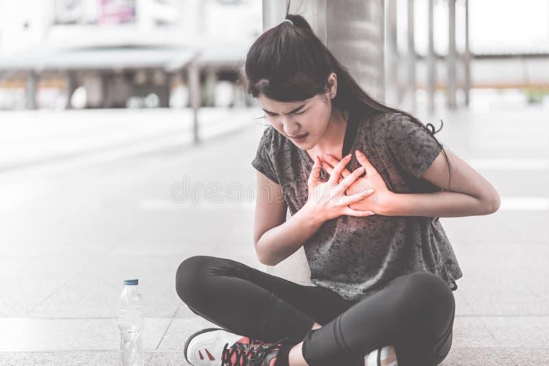 Sportkvinna som har en skada på hennes attac för hjärtabröstkorgsjukdom royaltyfri foto