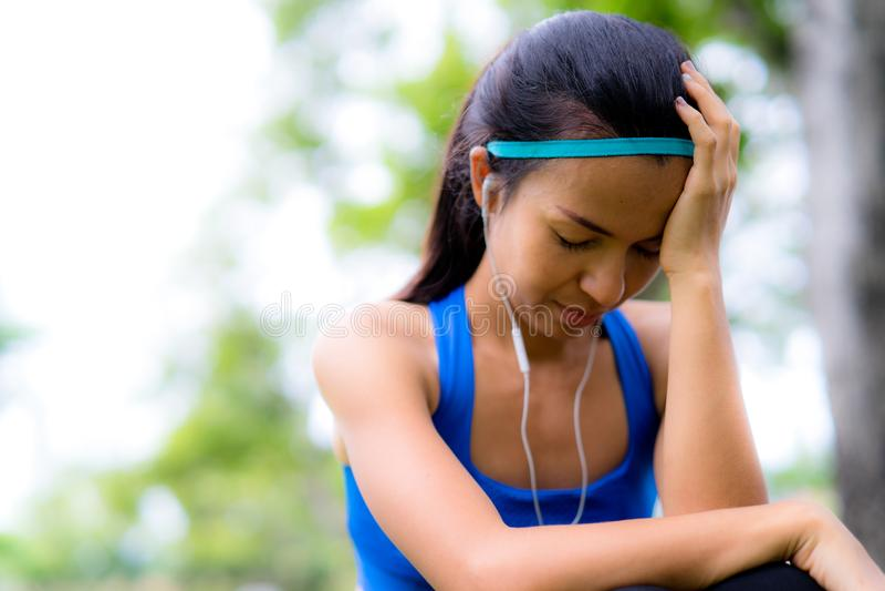 Sportkvinna som har huvudvärk efter övning i parkera fotografering för bildbyråer