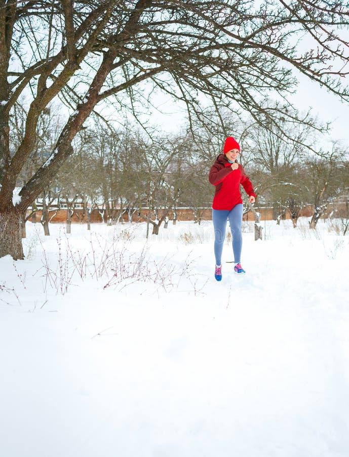 Sportkvinna som kör i vinter royaltyfri foto
