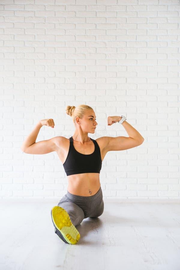 Sportkvinna som poserar i photostudio över tegelstenväggen Konditionmotivation fotografering för bildbyråer