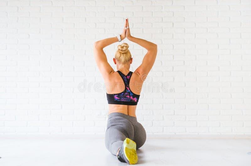 Sportkvinna som poserar i photostudio över tegelstenväggen Konditionmotivation arkivfoton