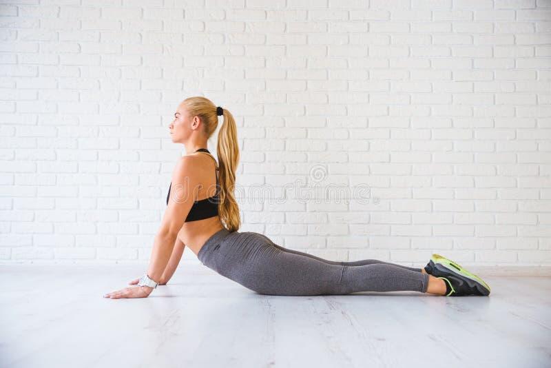 Sportkvinna som poserar i photostudio över tegelstenväggen Konditionmotivation arkivbild