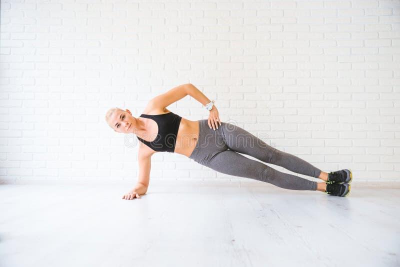 Sportkvinna som poserar i photostudio över tegelstenväggen Konditionmotivation royaltyfri fotografi