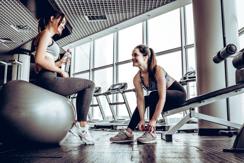 Sportkvinna som sitter och vilar efter genomkörare eller övning i konditionidrottshall royaltyfria bilder